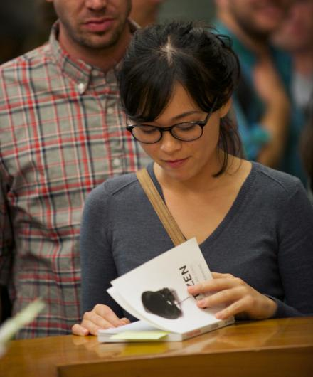 A reader paging through a copy of Citizen at an event at the Los Angeles Public Library